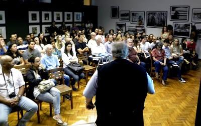 Palaestra Sociedade Fluminense de Fotografia. A foto está mostrando uma série de pessoas sentadas olhando para o palestrante que está de frente para eles e de costas para a foto