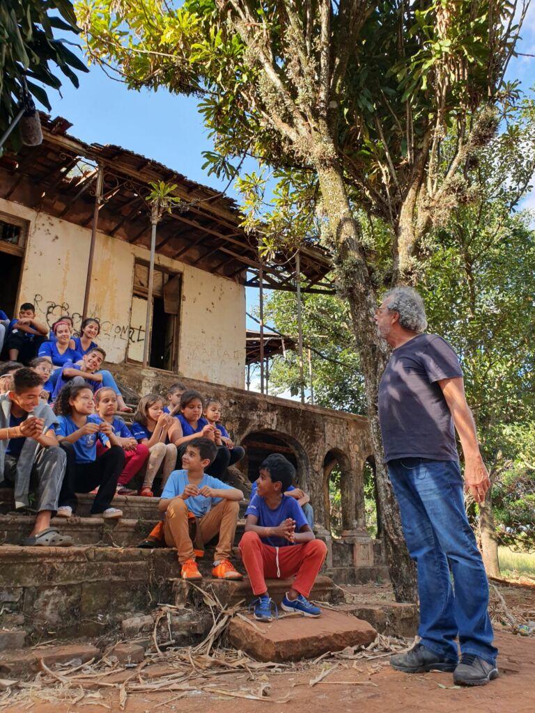 Dezenas de crianças sentadas na escadaria de uma casa em ruínas. Elas prestam atenção em um homem  grisalho de calça jeans e blusa cinza em frente a elas.