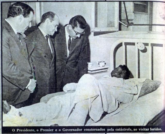 Foto de um arquivo de jornal de 3 políticos visitando uma vítima do incêndio no Gran Circus. Eles estão de pé e a vítima na cama de um hospital