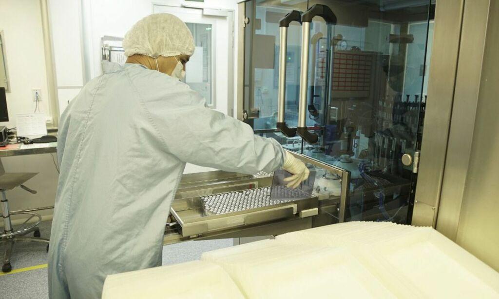 Homem com touca e luvas preparando vacinas dentro do laboratório da Fiocruz