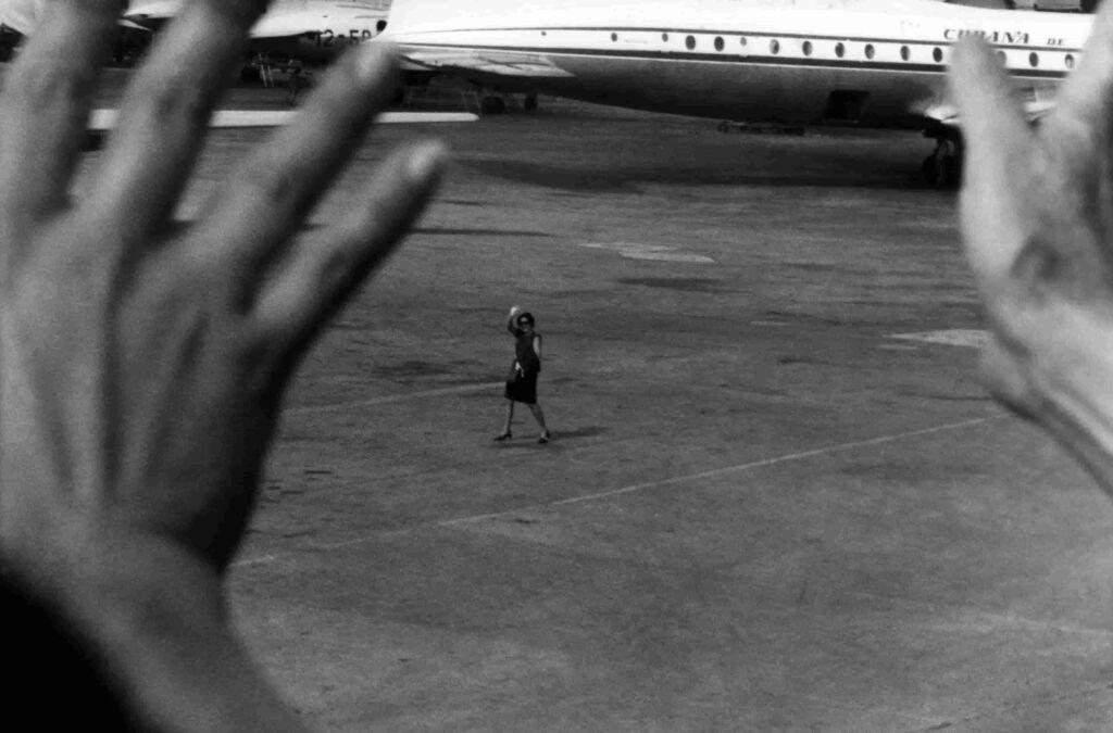 Fotografia de José Alberto Figueiroa, intitulada De la serie Exilio. Olga. La Habana, 1967, que estará no Museu do MAC em Niterói. Na fotografia  em primeiro plano está um mão dando adeus a uma mulher que está em segundo plano em uma pista de avião.