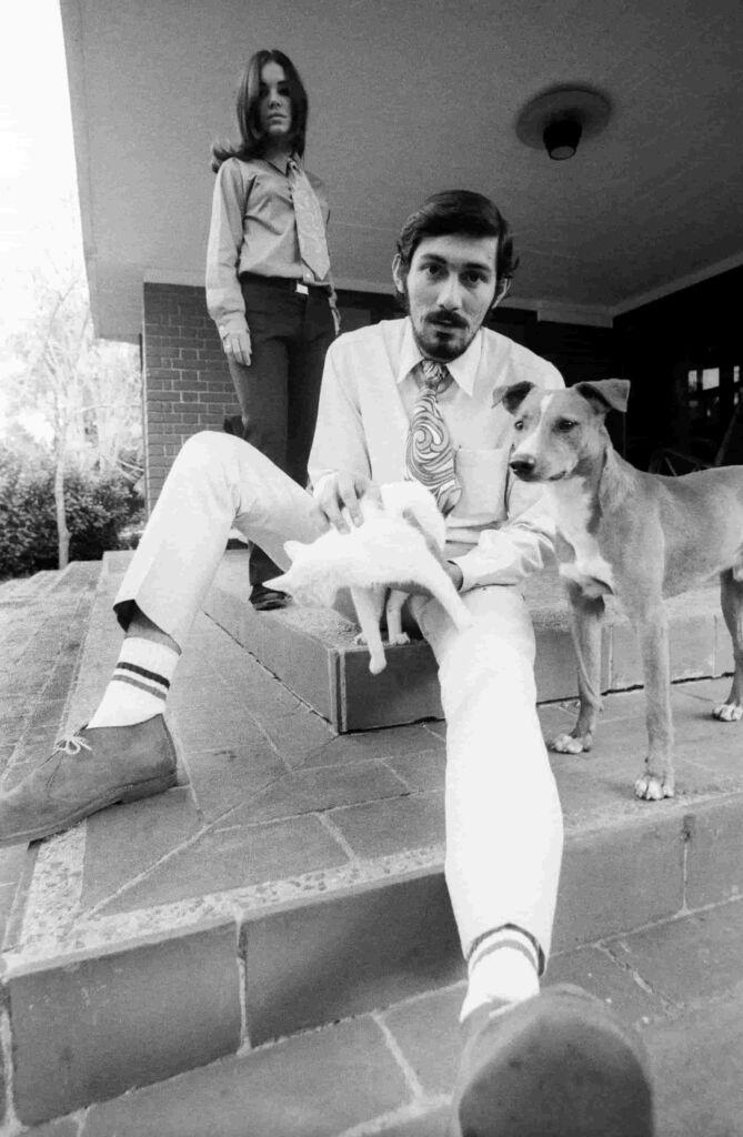 Fotografia de José Alberto Figueroa intitulada Diana y Navarro. La Habana, 1967. na fotografia em preto e branco está  um homem sentado com um gato na mão e um cachorro ao lado. Atrás está uma mulher.